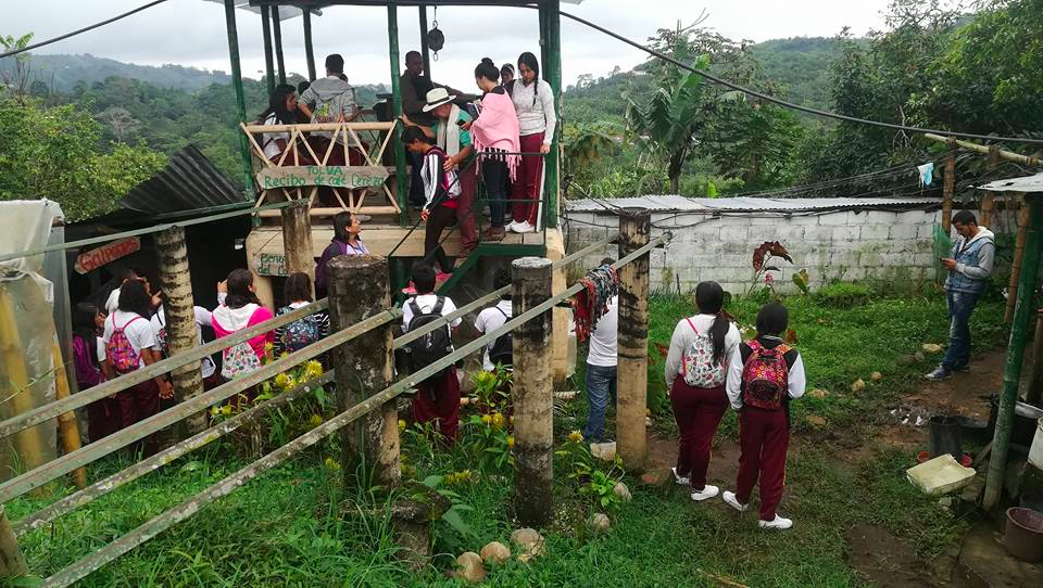 A photo showing students standing on and amongst structures on a farm with lush rolling green hills in the background.