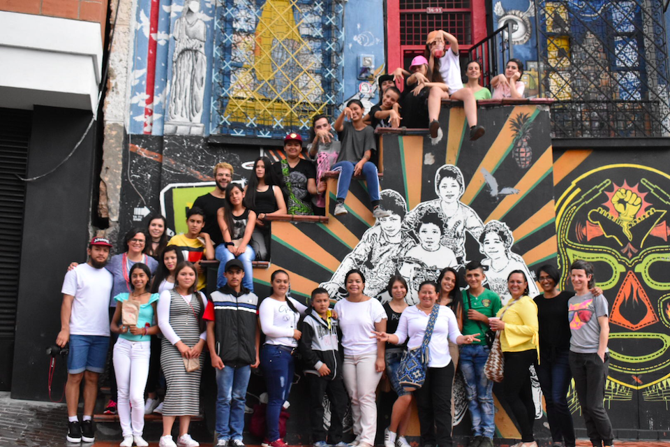 Group photograph of a large number of people posing in front of a colourfully painted building, some sitting on stairs and some standing in front